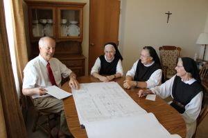Architect conferring with building commitee on plans for new church